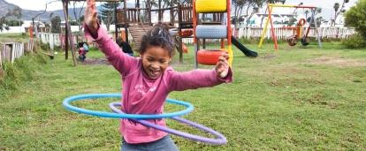 During a Childcare Project in South Africa, a young girl hula hoops outside a care centre.